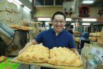 คุณ บัญชา ถือถาดขนมปังจากร้าน D.K. Bakery